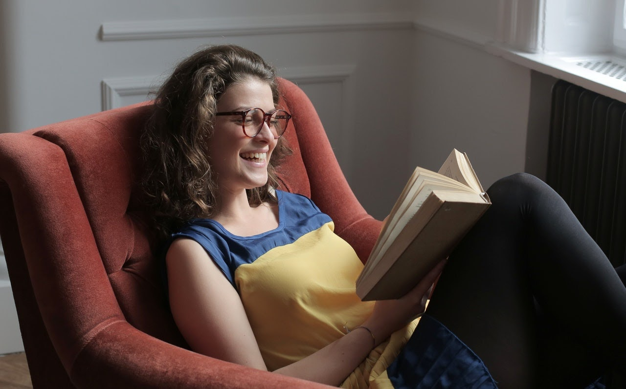 woman in chair laughing and reading