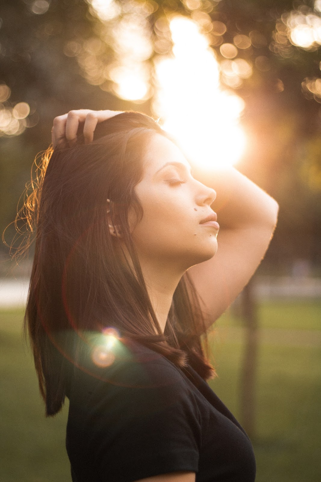 woman in sunlight breathing with eyes closed
