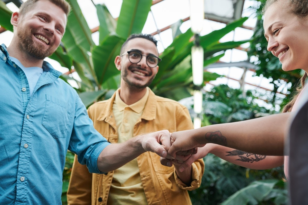 friends fist bumping in greenhouse