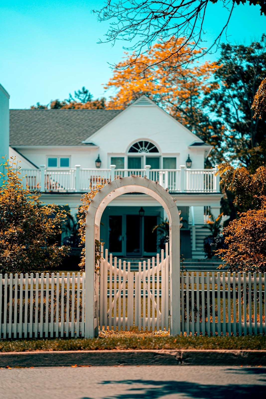 orange and teel house with clean white fence