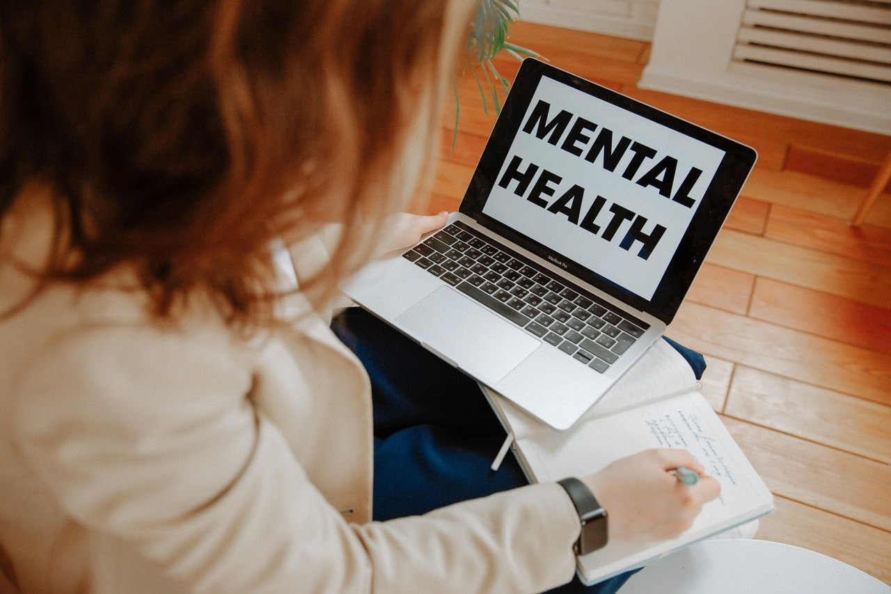 woman taking notes off a laptop with mental health on screen