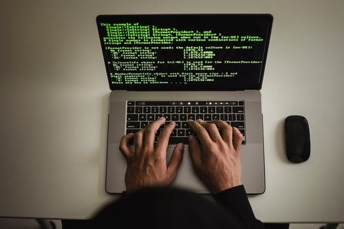 Crop faceless developer working on software code on laptop