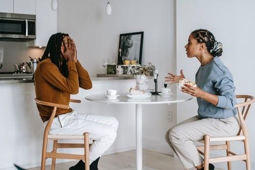 Multiethnic couple quarrelling at table in light apartment