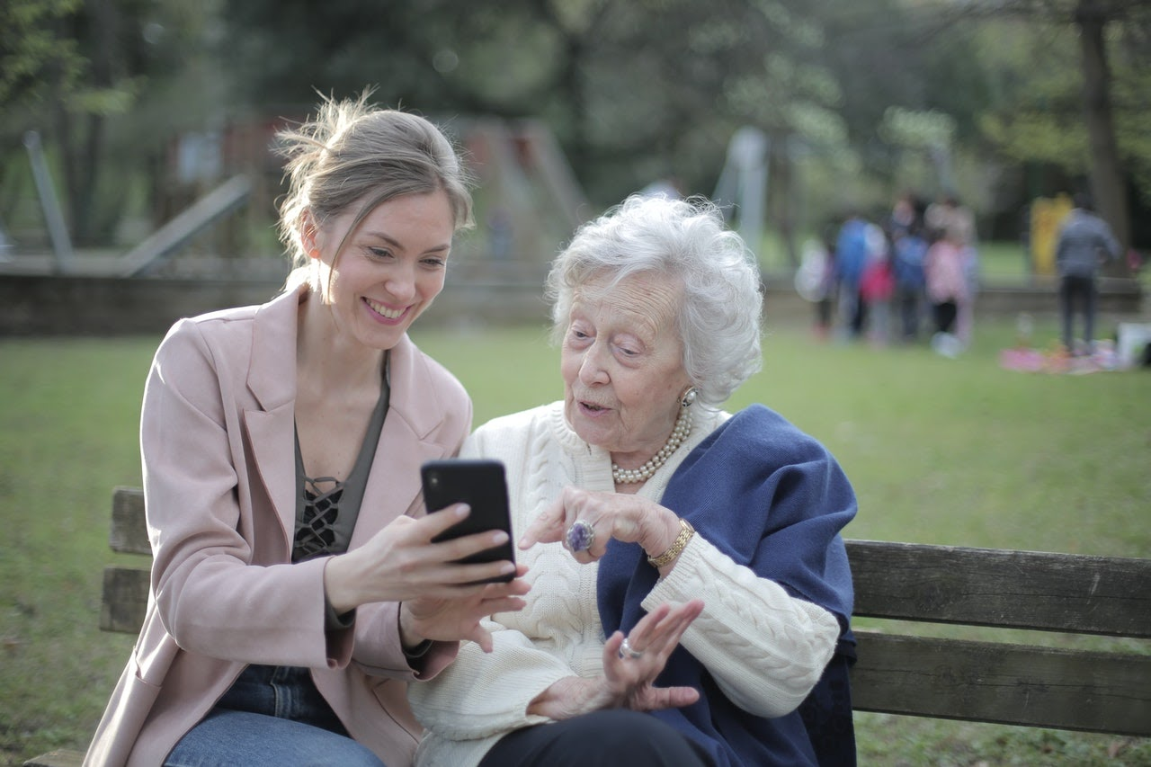 women showing phone to elder