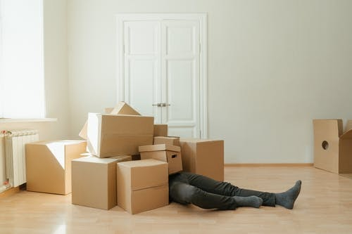 Person in Black Leather Boots Lying on Brown Cardboard Boxes