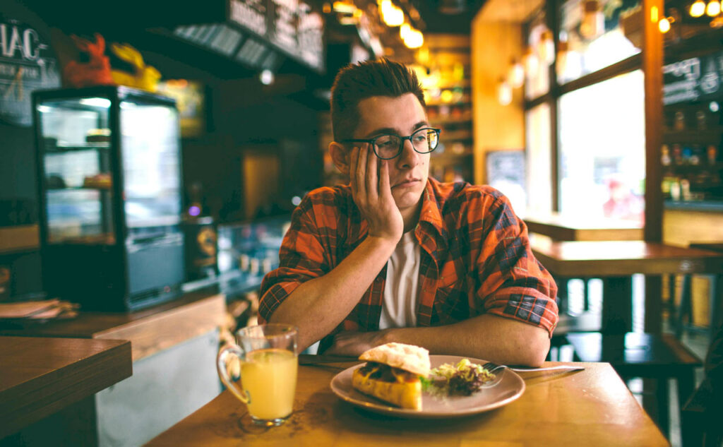 Eating Disorder Therapy -Man with no appetite sitting in restaurant