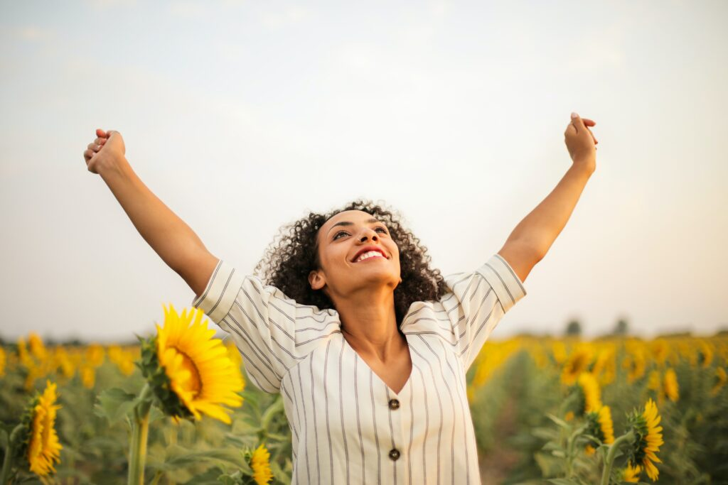 Woman smiling while running though a sunflower field.