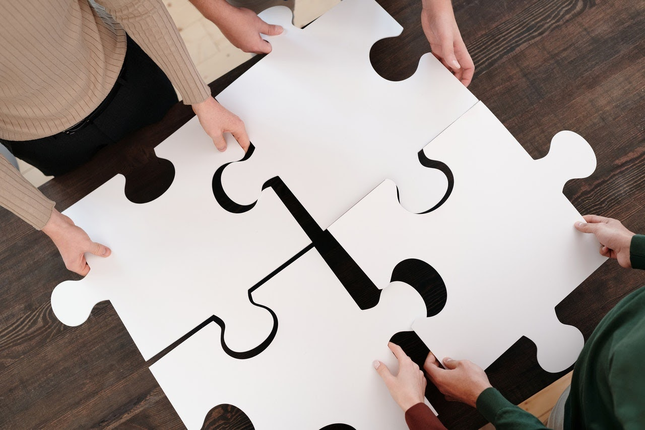 4 people holding puzzle pieces which fit together.